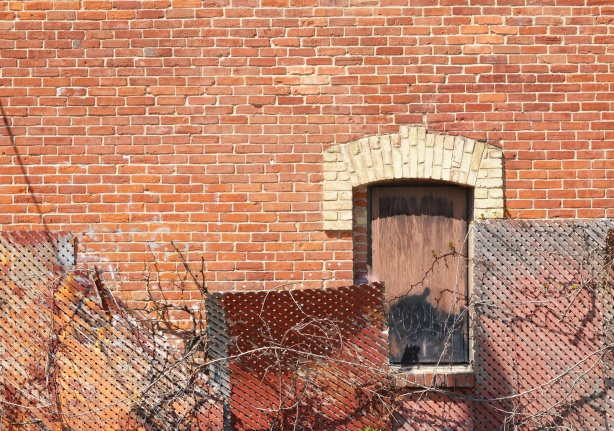 red brick wall, boarded up window with curved upper window frame, 4 wood trellises in front in different shades of rust and brown