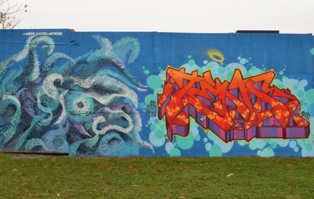 two murals side by side on blue hoardings, on the left is a blue monster by andre castro and on the right is an orange and red text graffiti
