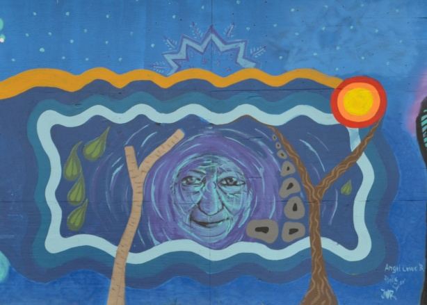 mural, an old woman's face in the middle, stylized brown trees, lines for earth and sky