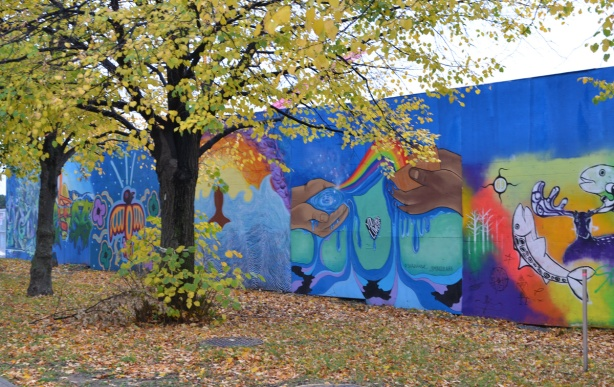 autumn trees in front of hoardings covered with murals, wallnoize, leaves on the ground,