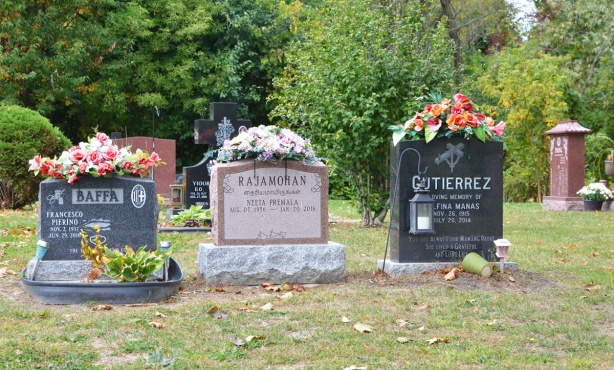 monuments, tombstones at Pinehills cemetery with flower arrangements on top of them