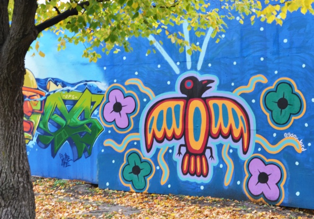 mural on hoardings near Ashbridge Bay water treatment facility, wallnoize project, indigenous art style bird facing upwards with flowers on both sides