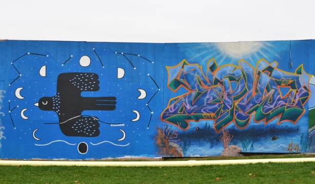 2 murals on hoardings, a stylized blackbird flying with the moon in different phases around it. on the right is a wildstyle