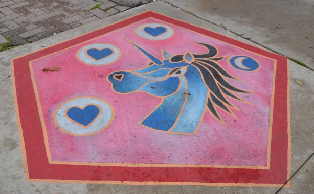 painting of a unicorn on the sidewalk, a blue unicorn surrounded by 4 blue hearts, all on a pink background, the work of whatsvictorupto