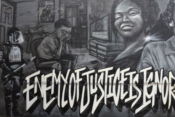 part of the Enemy of Justice mural, policeman standing by door, man sitting with hands over his eyes as TV is broadcasting about Breonna Taylor murder by policemen