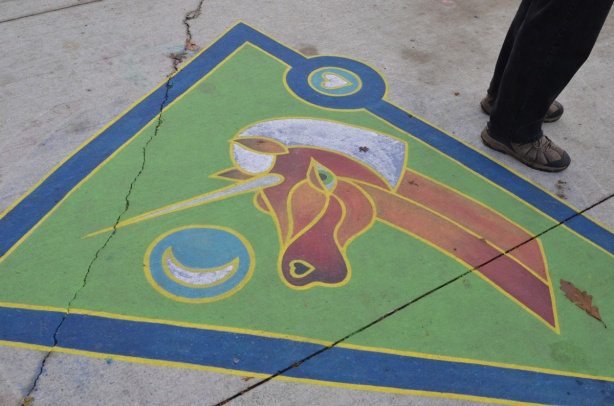 painting of a unicorn on the sidewalk, a brown unicorn head and neck with white mane and horn on a green background
