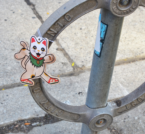 cat graffiti on cardboard, tied to Toronto circular bike stand