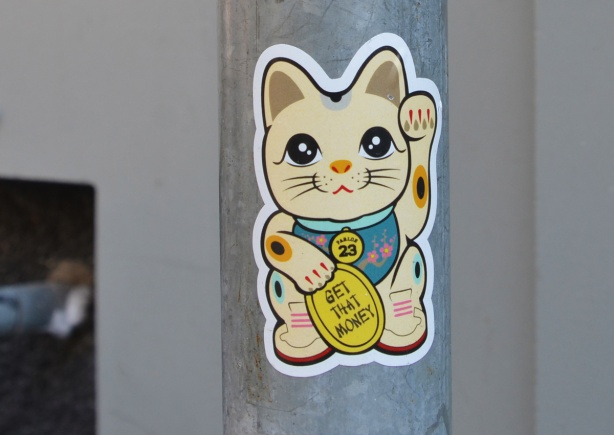 happy cat waving sticker, holding gold coin that says get the money