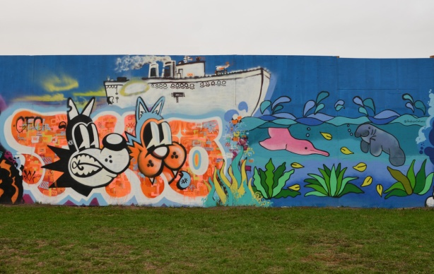 a dog and cat head in front of a large white boat in one of the two murals on hoardings around new water treatment plant by Ashbridges. other mural is a pink dolphin and a blue narwhal playing in the water
