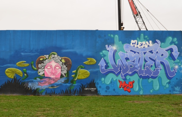two murals on hoardings around new water treatment plant by Ashbridges, on the left a very pink faced lady with grey curly hair in the water with little green dragons and lily pads. on the right, text painting that says clean water H 2 O