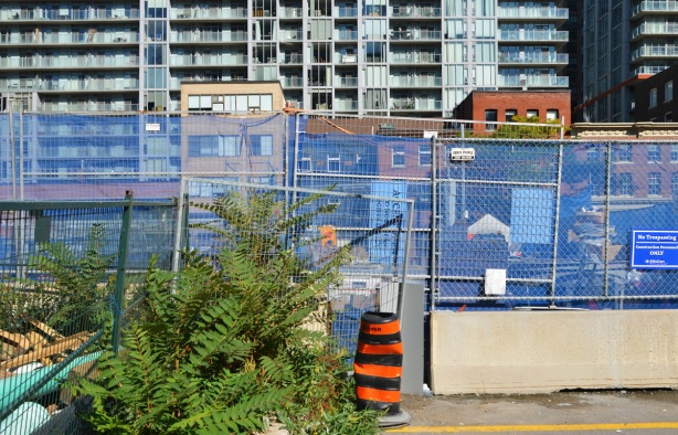 blue construction fence around a hole at a work site, row of storefronts across the street in the next level and a tall apartment building behind that