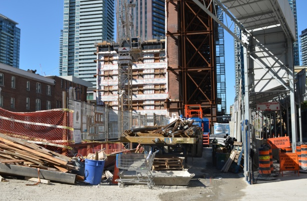 construction site, preservation of large brick facade held up by rust coloured metal beams and scaffolding