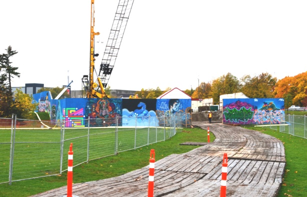 truck and vehicle entrance to construction site, orange cones, wire fence, hoardings,