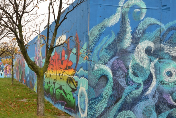 looking along a wall of murals on blue hoardings