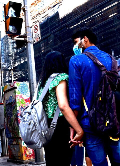 a couple walking on Yonge Street, holding hands, waiting for a light to change, he's in a blue shirt and wearing a covid mask