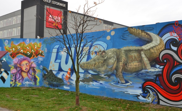 wallnoize street art murals on blue hoardings around new water treatment plant, a crocosile, very realistic looking, by luvs, with its feet in water