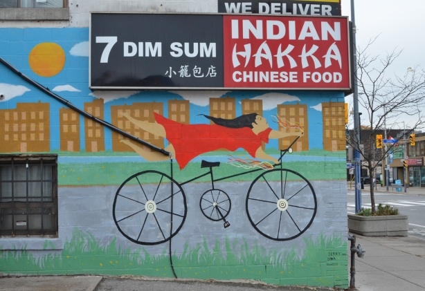 on the side of a Chinese restaurant, a mural of a woman on a bike. She's holding the handle bars but her legs are straight out behind her. She's wearing a red dress and has long black hair. There are three signs on the restaurant, First, Indian Hakka Chinese Food, second, 7 dim sum, and third, we deliver