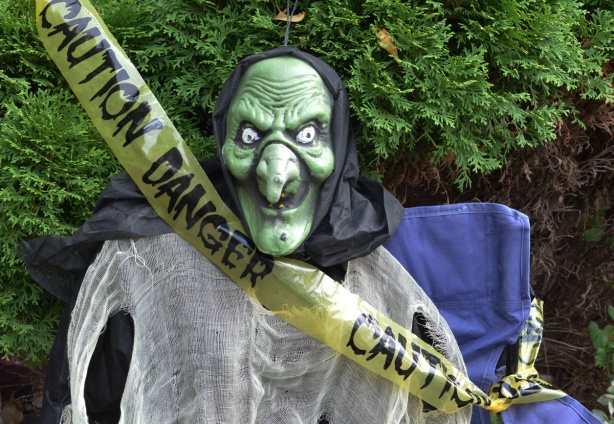 yellow caution danger tape crosses in front of a green ugly mask on a white cloth