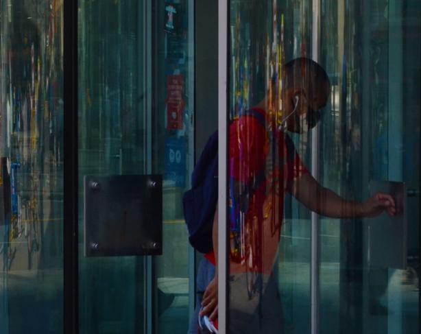 a man walks through a glass revolving door, reflections,