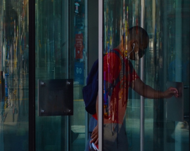 a man walks through a glass revolving door, reflections,