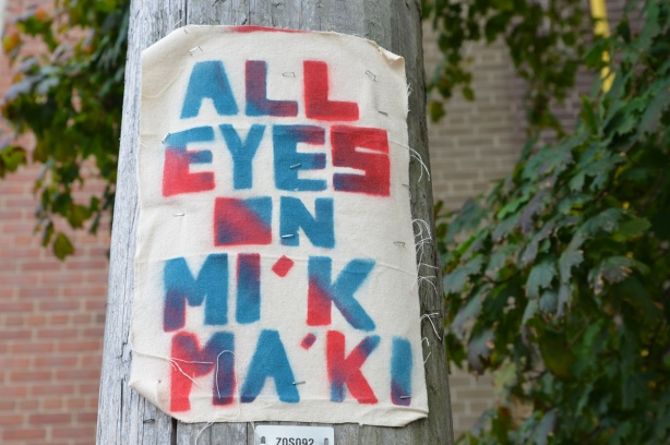on a wood utility pole, a poster made of fabric that says All Eyes on Mi'kma'ki