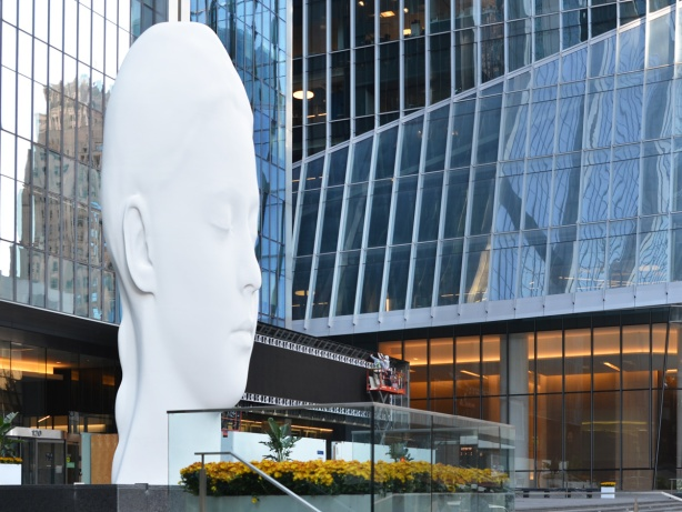 large three storey high white sculpture of a woman's face with her eyes closed, title is Dreaming and the artist is Jaume Plensa