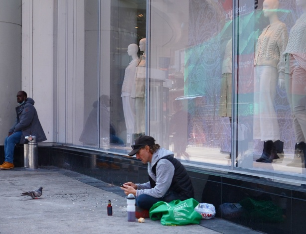 windows of H & M store at yonge and Dundas, with femaile mannequins, sitting on the sidewalk in front of them is a man feeding pigeons, another man sits nearby