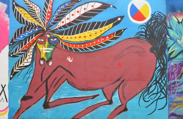 a brown horse with mane that lookslike coloured feathers, face painted in primary colours, mural