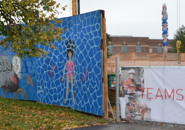 hoardings around a construction site, beside vehicle entrance, a mural of a woman in a pink bathing suit floating on her back in a pool