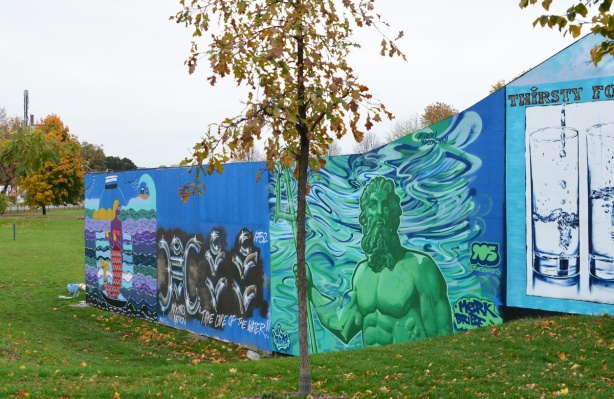 a small tree in front of murals on hoardings near Ashbridge Bay water treatment facility, wallnoize project,
