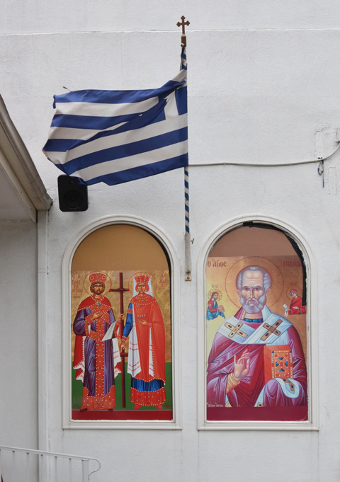 2 pictures, exterior, front of Greek Church, white walls, with a Greek flag flying between the two of them
