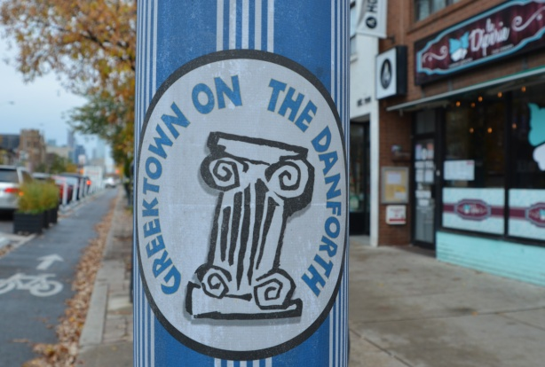 a utility pole on the street decorated for Greektown, in blue and white vertical stripes and an oval with the words Greektown on the Danforth along with a Roman column