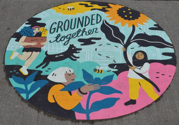 a painting on the sidewalk, a circle with words grounded together, pictures of women with plants and flowers, a dog chasing a bird.