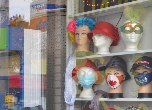 two shelves with head mannequins, wearing different wigs, covid masks, hats, and halloween masks