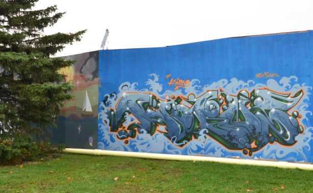 wildstyle mural on blue hoardings, pine tree beside
