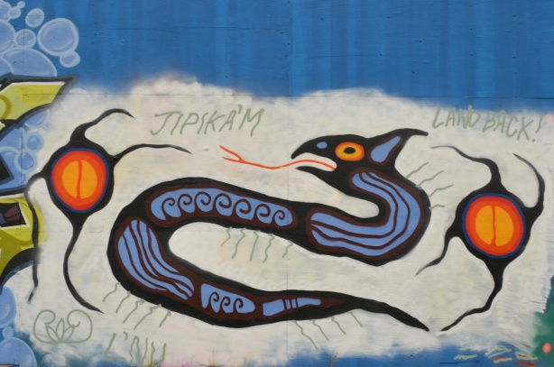 Jipik'am mural of a snake with tongue out, first nations symbols, words that say land back
