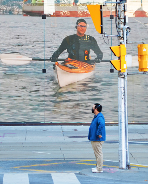 a man in a blue jacket stands in front of a large video screen at Queen and Bay, video of a man in an orange and white kayak is playing