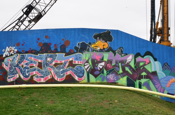 a duck character looks over the top of two text based graffiti murals one says kerz and the other is by bubzart