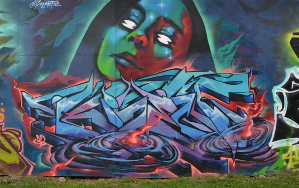 water treatment facility construction hoardings, mural, by kizmet 32, a woman's face in green, blue and red, on top of a textual