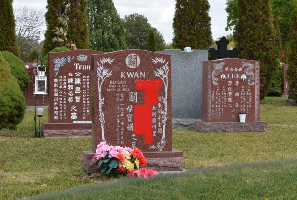 Chinese tombstones in Pinehills cemetery, in Manadarin, one red tape over part of one stone