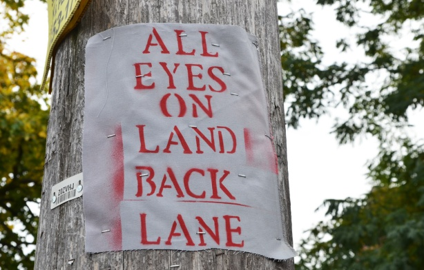 on a wood utility pole, a poster made of fabric that says All Eyes on Land back Lane
