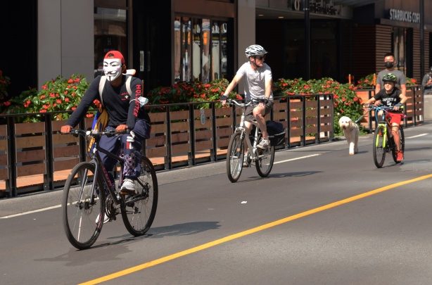 three people on bikes on Yonge street during streets open, the man in front is wearing an anonymous mask