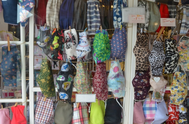 fabric covid masks for sale in the window of a store