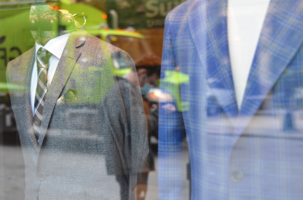 reflections of a man in the window of a mens clothing store, two suits on display, one gray and one blue.