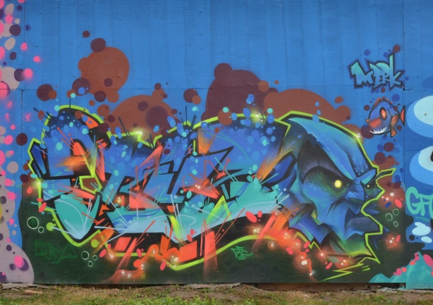 mural by Cruz 1 on hoardings around a construction site near Ashbridges, a blue face and lots of colours around word that says Cruz, plus a tiny fish in top right