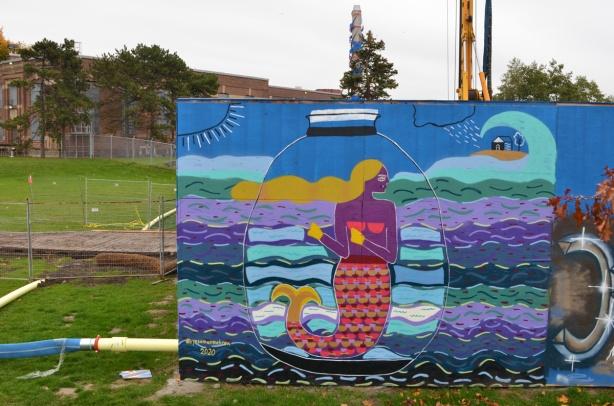 mermaid in a jar in the water, a mural