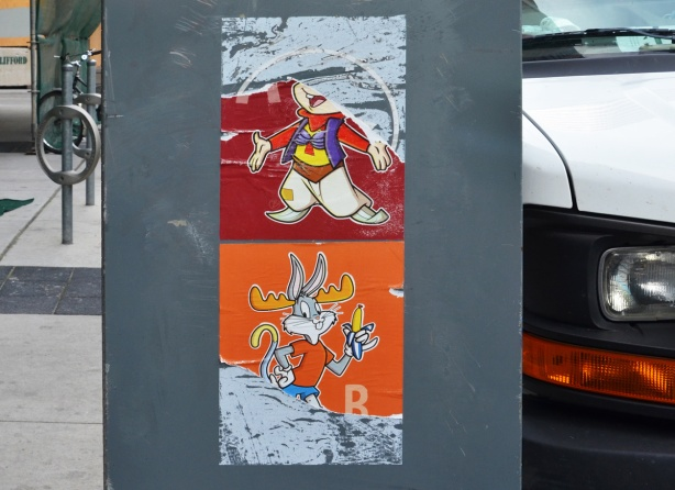 two coloured posters on a box on the street, both torn. On top, on red background is bugs bunny. on bottom on orange background is bugs bunny eating a banana