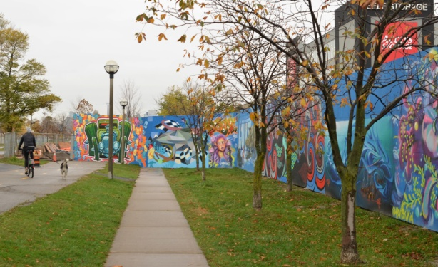 looking along a wall of murals on blue hoardings to where they cross and block the sidewalk