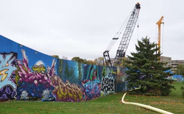 pine tree beside hoardings around a construction site that have been painted by wallnoize, a group of street artists who have each painted a mural on a section of the wall