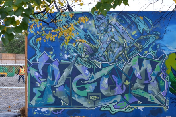 mural on hoardings near Ashbridge Bay water treatment facility, blues wildstyle with man that looks like he's made of water, on a skateboard